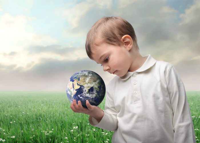 Child holding the earth with green meadow on the background