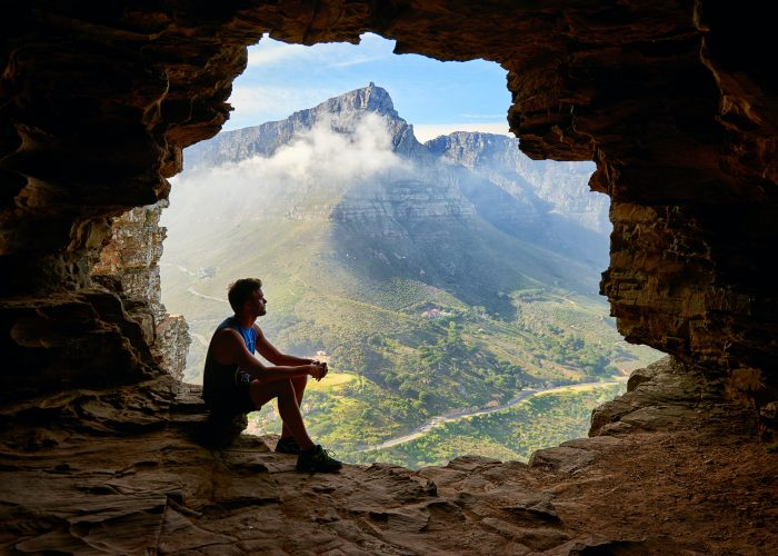 photo-of-man-sitting-on-a-cave-1659437